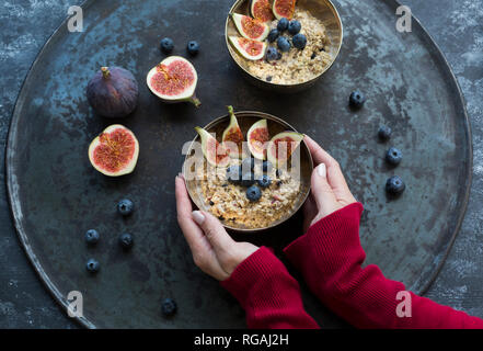 Woman's hands holding bowl of porridge with sliced figs, blueberries and dried berries - Stock Photo