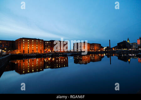 Buildings of the Royal Albert Dock reflect in the Salthouse Dock in Liverpool, England. The dock on the River Mersey is the oldest in Liverpool. - Stock Photo