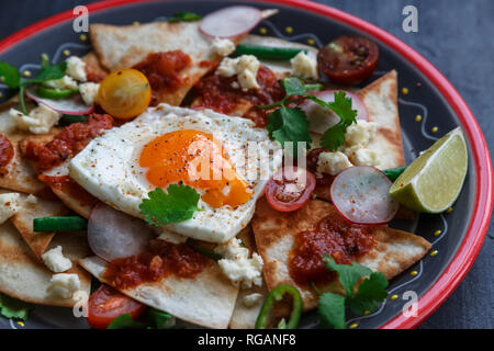 Mexican breakfast: chilaquiles with egg, avocado and vegetables close-up on a plate - Stock Photo