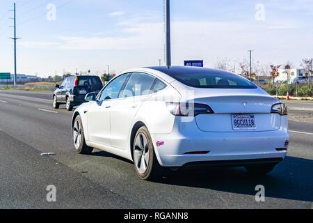 January 27, 2019 Santa Clara / CA / USA - White Tesla Model 3 driving on the freeway in Silicon Valley, south San Francisco bay area - Stock Photo