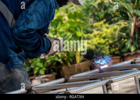The welder is welding the steel frame. Labor and industrial work hard. - Stock Photo