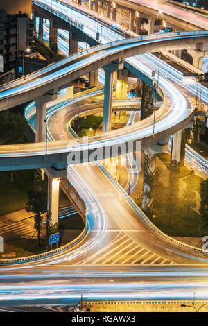 Urban elevated road junction and interchange overpass at night in Chengdu, China - Stock Photo