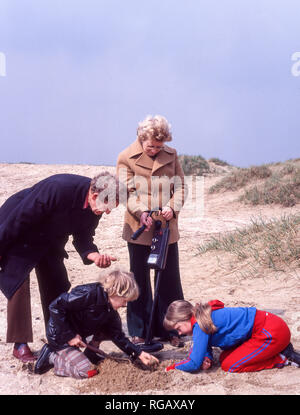 Grandparents with two grandchildren using a metal detector on a beach in northwest England. - Stock Photo