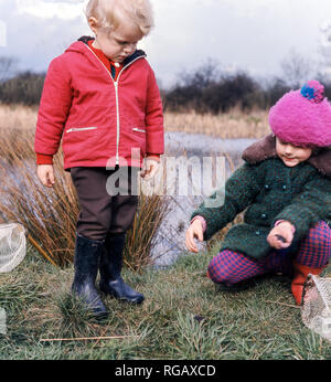 Two young children ( a boy and a girl) trying some pond dipping at the Attenborough Nature Reserve near Beeston Nottingham. - Stock Photo