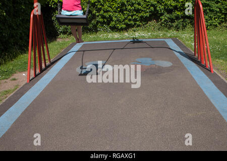Two caucasion girls playing on swings in a park in a playground, 1 in shadow - Stock Photo