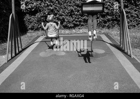 black and white photograph of two caucasion girls playing on swings in a park in a playground - Stock Photo
