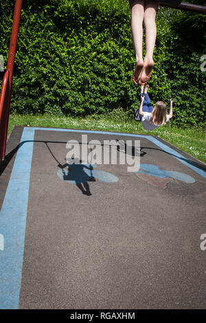 Two caucasion girls playing on swings in a park in a playground with their shadow - Stock Photo