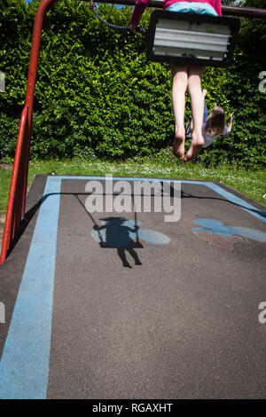 Two caucasion girls playing on swings in a park in a playground with shadow - Stock Photo