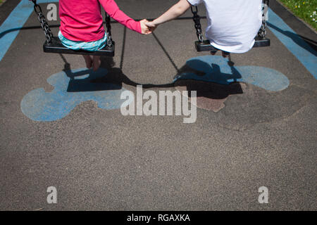 Two caucasion girls playing on swings in a park in a playground - Stock Photo