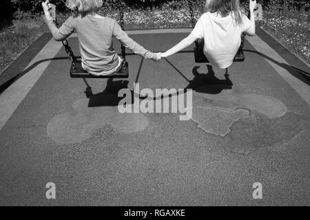 b;acl and white photograph of Two caucasion girls playing on swings in a park in a playground - Stock Photo