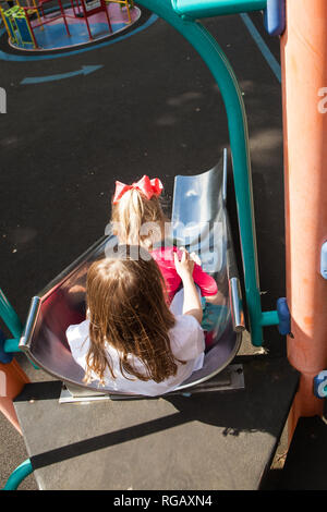 two caucasion girls on a slide in a playground - Stock Photo