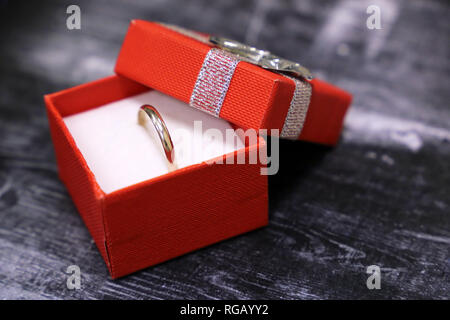 Gift box with golden ring on vintage wooden table. Concept of marriage proposal, jewelry, Valentines gift, romantic present - Stock Photo