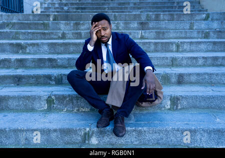 Young fired african american business man lost in depression crying sitting on ground street stairs suffering emotional pain sadness in grunge lightin - Stock Photo