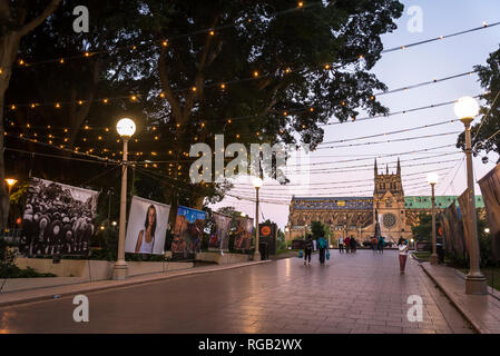 People passing by Australian Life Photography exhibition in Hyde park and St Mary's Cathedral in the background, Sydney, Australia - Stock Photo
