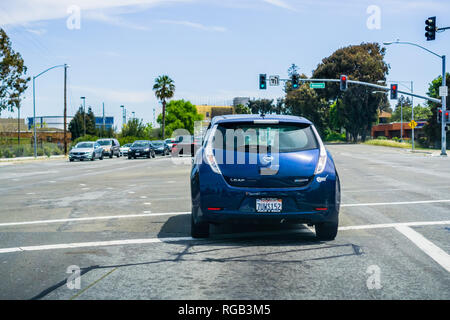 April 22, 2018 Santa Clara / CA / USA - Back view of Nissan Leaf about to make a left turn at a traffic junction in south San Francisco bay area, Sili - Stock Photo