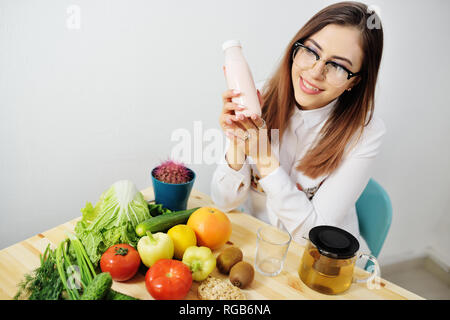 young cute girl with glasses holding yogurt or kefir in a bottle on the background of a table with lots of vegetables - Stock Photo