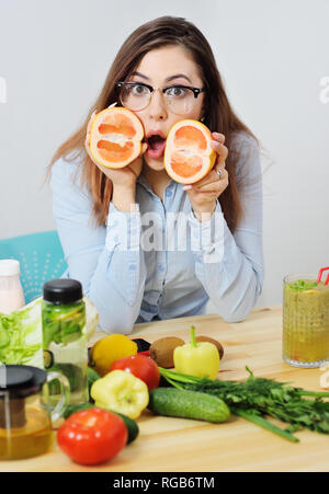 beautiful young girl holding a cut grapefruit in her hands on the background of a table with vegetables - Stock Photo