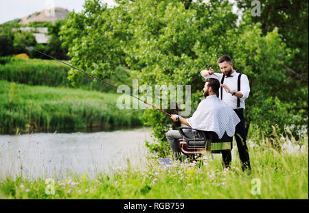 a professional hairdresser or Barber cuts the hair of a client in a Barber chair with a fishing rod in his hands on the background of greenery, trees, river and Park. - Stock Photo