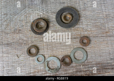 A happy face arranged from rusty metal washers placed on a rough piece of light grey timber. - Stock Photo