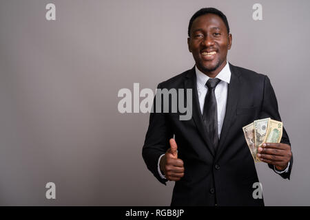 Young handsome African businessman holding money and smiling - Stock Photo