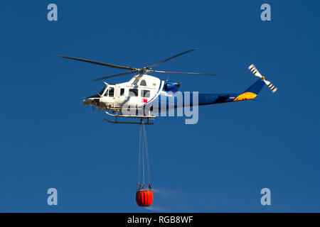 Helicopter extinguishing forest fires, heading to a fire spilling water from a basket that transports. - Stock Photo