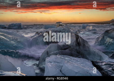 Raging heavy sea and winter storm makes large splashes and large waves on the huge ice blocks at the shore of North Atlantic Ocean at the famous glaci - Stock Photo