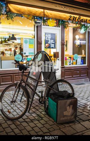 STRASBOURG, FRANCE - DEC 27, 2017: East 231 Burger restaurant cafe with Deliveroo bike and bag parked near the entrance driver pick-up the order - Stock Photo
