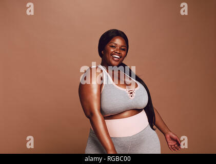 Large african woman looking happy on brown background. Plus size female in sports clothing looking at camera and laughing. - Stock Photo