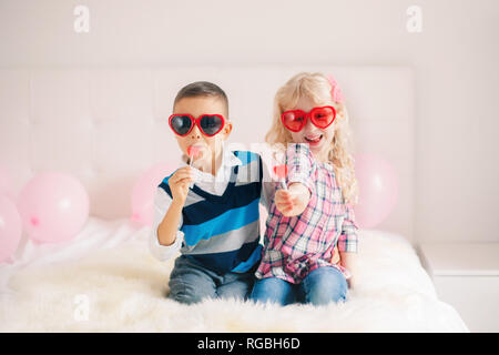 Group portrait of two happy white Caucasian cute adorable funny children eating heart shaped lollipops. Boy and girl celebrating Valentine Day. Love,  - Stock Photo