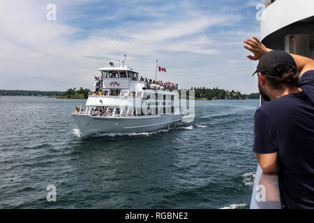 Thousand Islands National Park, Saint Lawrence River, Ontario, Canada, June 17, 2018: Young man in a boat cruise, waving towards other tourists' boat - Stock Photo