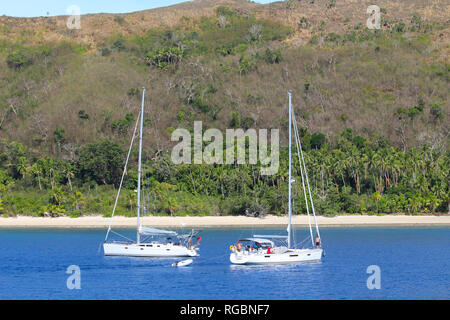 Two sailboats anchored in an island of the Yasawa, Fiji - Stock Photo