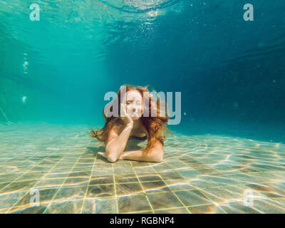 Woman at the bottom of the pool, she dives under the water - Stock Photo
