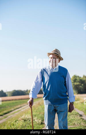 Senior man with a walking stick, walking in the fields - Stock Photo
