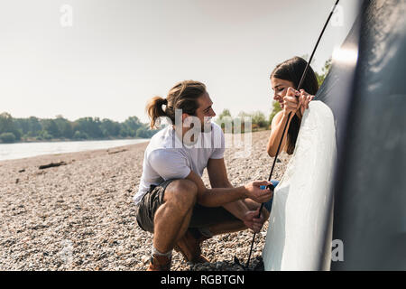 Smiling young couple setting up a tent at the riverside - Stock Photo