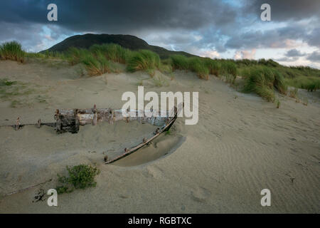 Carcass of a wrecked fishing boat buried in the sand of Glassilaun Beach. Connemara. County Galway, Ireland. - Stock Photo