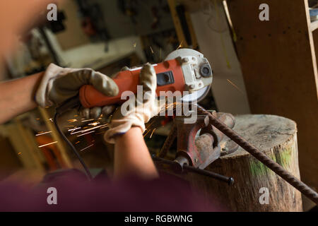 Craftswoman using angle grinder in her workshop - Stock Photo