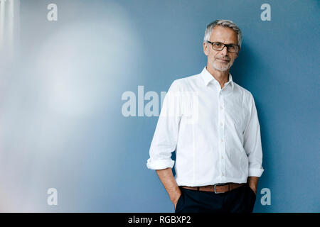 Portrait of a confident businessman with hands in pockets - Stock Photo