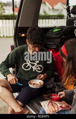 Young couple preparing sausages on a camping stove - Stock Photo