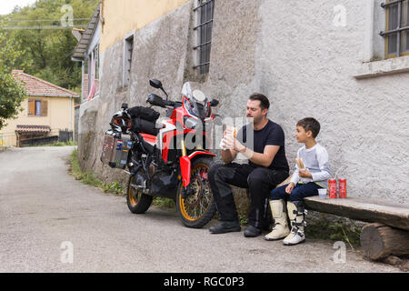 Father and son having a lunch break during a motorbike trip - Stock Photo