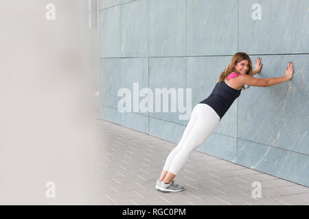 Smiling young woman leaning against wall doing stretching exercises - Stock Photo