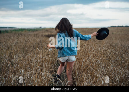 Back view of young woman with beverage and hat walking in corn field - Stock Photo