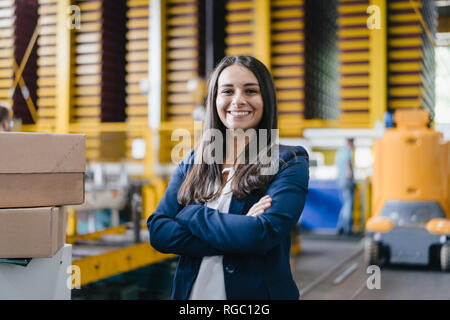 Confident woman standing in logistics center, with arms crossed