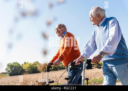 Two old friends walking on a country road, using wheeled walkers - Stock Photo