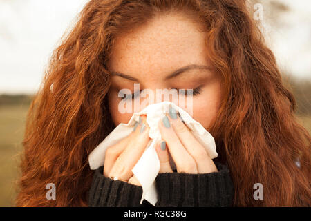 Redheaded young woman blowing nose in nature - Stock Photo