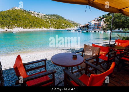 Tables with chairs of cozy Greek tavern restaurant in front of the beach in Assos village on Kefalonia island in Greece on summer morning - Stock Photo