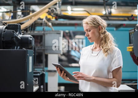 Woman using tablet at machine in factory shop floor - Stock Photo