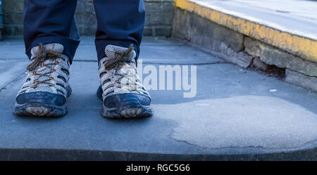 A pair of adult male feet wearing trainers. - Stock Photo
