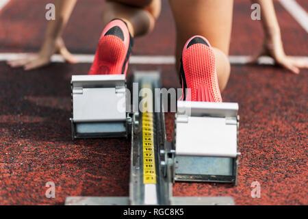 Teenage runner kneeling on starting block, close up