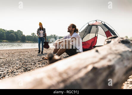 Young couple relaxing at the riverside with guitar and tent - Stock Photo