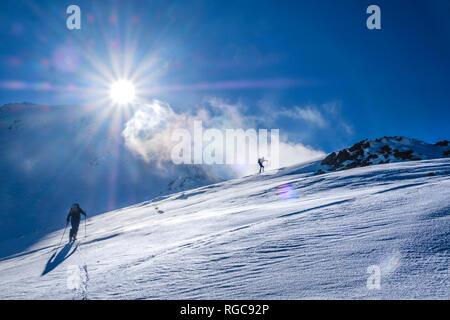 Two men doing a ski tour in Faragas mountains, Southern Carpathians, Romania - Stock Photo